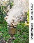 kindling samovar on firewood.... | Shutterstock . vector #1053015860
