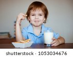 a cute little boy in a blue t... | Shutterstock . vector #1053034676
