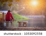 Small photo of The shadow of a young red-shirted man sitting in a beautiful waterfront garden in the morning, with loneliness and sadness waiting for someone to come back. The concept of loneliness and spiritless