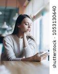 young caucasian girl sitting in ... | Shutterstock . vector #1053130640