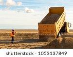 dump truck is moving down sand... | Shutterstock . vector #1053137849