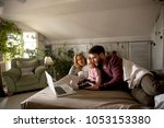 happy family lies on bed and... | Shutterstock . vector #1053153380