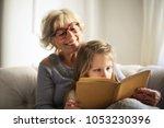 grandma and grandaughter reading | Shutterstock . vector #1053230396