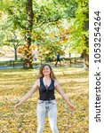Manhattan New York City NYC Central park, young hipster millennial woman standing, throwing many fallen leaves up in air in autumn fall season with yellow foliage