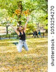 Manhattan New York City NYC Central park, young hipster millennial woman jumping, many fallen leaves up in air falling in autumn fall season with yellow foliage