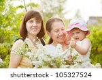 Happy women and kid in plant at summer garden - stock photo