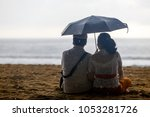 Couple Sitting By Sea With An...