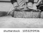 Greyscale image of the gloved hands of a manuel worker laying outdoor paving slabs on a prepared base.