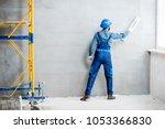 plasterer in blue working... | Shutterstock . vector #1053366830