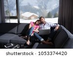 young couple relaxing at  home... | Shutterstock . vector #1053374420