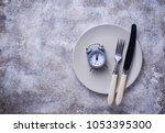 grey alarm clock in empty plate.... | Shutterstock . vector #1053395300