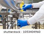 worker at bottling factory... | Shutterstock . vector #1053404960