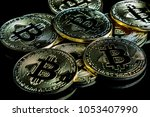 A bitcoin concept with tokens on a black background to represent the dark use of the currency - stock photo