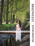 Small photo of A lovely brooding brunette girl with long hair in a white romantic dress alone sits on a small bridge in a spring forest or Park. Vertical picture.