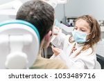 Small photo of Child in a mask in the role of a dentist is treating teeth to an adult male