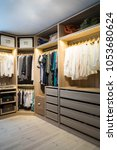 Small photo of Luxury walk in closet / dressing room with lighting and jewel display. Dresses, handbags, blouses and sweaters on hangers in the wardrobe. Vertical.