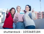 Small photo of Portrait of three young happy girls sitting together and gesturing