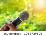 microphone in hand for singing... | Shutterstock . vector #1053739508