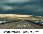 carpe diem - confidence - dark clouds hang low over a highway
