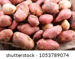 fresh potatoes on a wooden... | Shutterstock . vector #1053789074