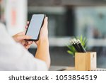 man holding smart phone with... | Shutterstock . vector #1053854519