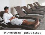 a young handsome man lies on a... | Shutterstock . vector #1053951593