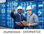 two engineers wearing hardhats... | Shutterstock . vector #1053965723