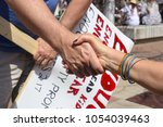 Stock photo two teachers clasping hands with protest sign in background at march for our lives rally in tulsa 1054039463