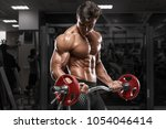 muscular man working out in gym ... | Shutterstock . vector #1054046414