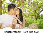 Man and woman kissing under the lilac bush - stock photo