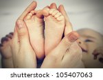 Small Feet Baby Holds His...