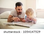 father and daughter laying on... | Shutterstock . vector #1054147529