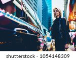 charming young woman strolling... | Shutterstock . vector #1054148309