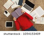 exhausted student girl lying on ... | Shutterstock . vector #1054153409