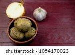 whole baked potatoes in a plate ... | Shutterstock . vector #1054170023