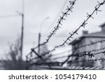 barbed wire fence enclosing the ... | Shutterstock . vector #1054179410