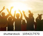 hands up against sunset... | Shutterstock . vector #1054217570
