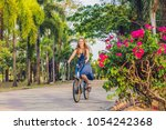 young beautiful woman riding a... | Shutterstock . vector #1054242368