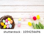 colorful easter eggs in nest... | Shutterstock . vector #1054256696