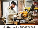the young carpenter works in a... | Shutterstock . vector #1054294943
