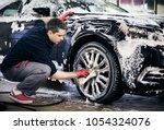 man worker washing car's alloy... | Shutterstock . vector #1054324076