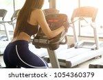 woman exercise bike cardio... | Shutterstock . vector #1054360379