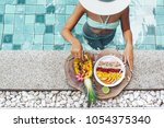 girl relaxing and eating fruit... | Shutterstock . vector #1054375340