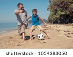 father and son playing football ... | Shutterstock . vector #1054383050
