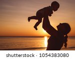 mother and baby son  playing on ... | Shutterstock . vector #1054383080