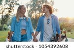 young couple with skateboards...   Shutterstock . vector #1054392608