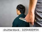 Small photo of Knife hand hold with man sitting, backstabbing