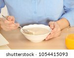 woman with vanilla pudding at... | Shutterstock . vector #1054415093