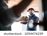 woman receiving parcel from... | Shutterstock . vector #1054476239