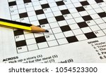 Small photo of Closeup of crossword puzzle from a newspaper with a black and yellow lead pencil